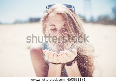 Beautiful girl blowing sand with hands on the beach
