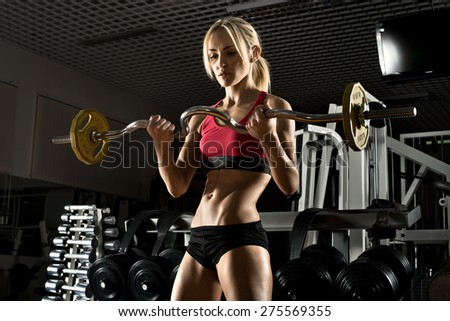 beautiful girl bodybuilder ,  execute exercise with  weight, in dark gym - stock photo