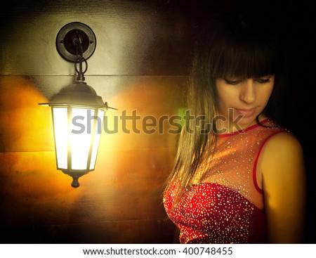 Beautiful girl, brunette, lantern light lit lowered her eyes - stock photo