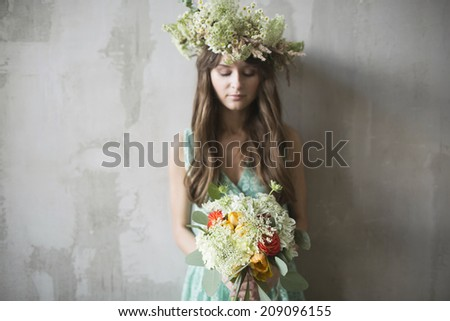 beautiful girl, brunette with a bouquet of flowers and a wreath in her hair - stock photo