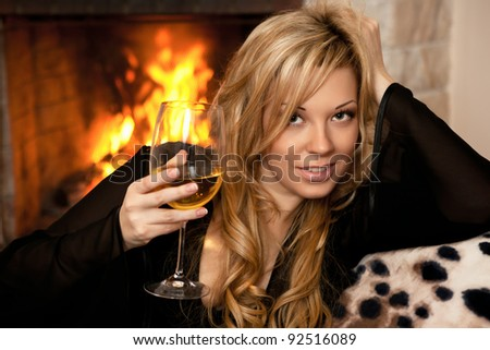 beautiful girl by the fireplace in the winter night - stock photo