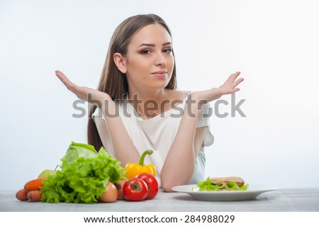 Beautiful girl can not choose between healthy and unhealthy food. She gesturing and looking at the camera confused. The girl is sitting at the table. Isolated on a white background - stock photo