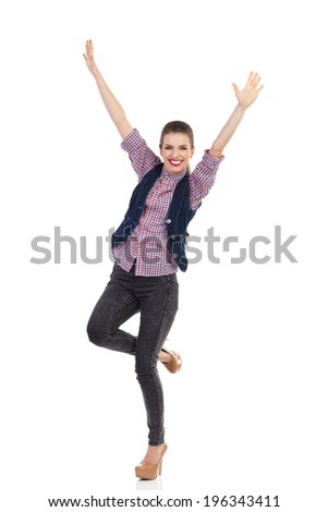 Beautiful girl celebrating success. Happy young woman is standing on one leg with arms raised. Full length studio shot isolated on white.