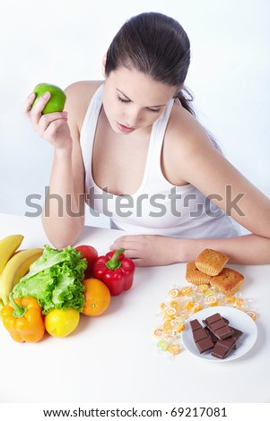 Beautiful girl choose between healthy food and sweet on a white background - stock photo