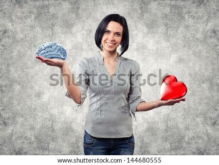 Beautiful girl chooses between brain and love - stock photo