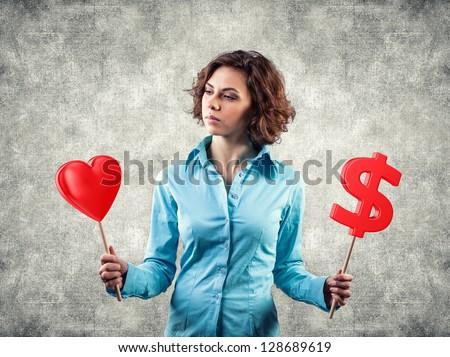 Beautiful girl chooses between money and love - stock photo