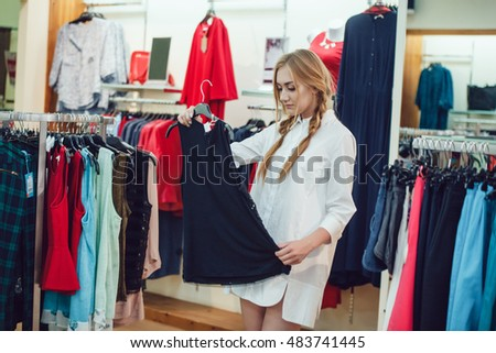 Beautiful girl chooses clothes in shop