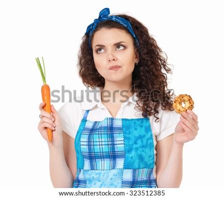 Beautiful girl choosing between fresh carrot and cookie - stock photo