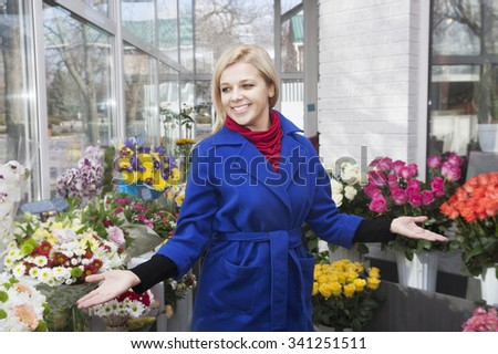 Beautiful girl choosing flowers in a flower shop