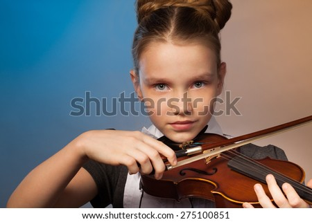Beautiful girl close-up view playing on the violin - stock photo
