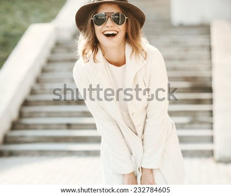 Beautiful girl close up with a hat laughing on a sunny day - stock photo