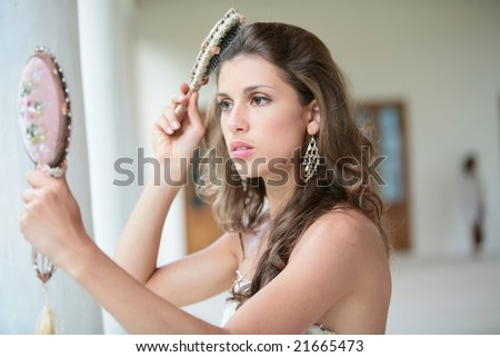 beautiful girl combs hairs and looks at itself in old-time mirror