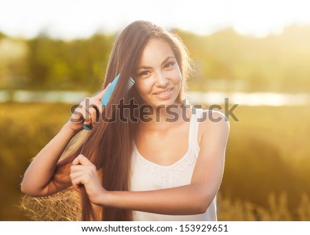 beautiful girl combs her hair Asian appearance  - stock photo