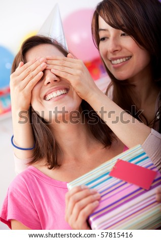 Beautiful girl covering her friend's eyes and giving her a brithday present - stock photo