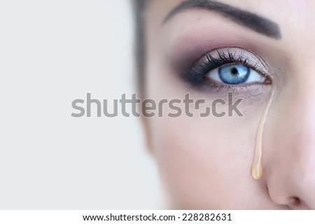 Beautiful girl crying. Tears. Female eye with a tear. Macro eye. - stock photo