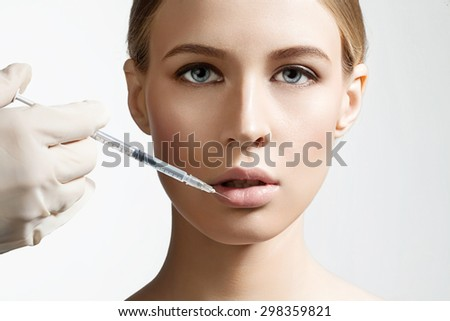 Beautiful girl doing an injection to increase the lips on a white background - stock photo