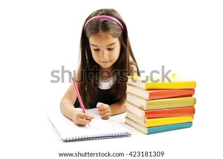 Beautiful girl doing her homework. Isolated on white background - stock photo