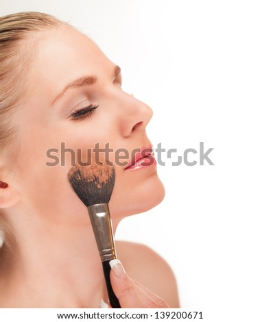Beautiful girl doing make-up, isolated on white background - stock photo
