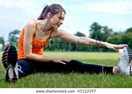 Beautiful girl doing stretching at the park - stock photo