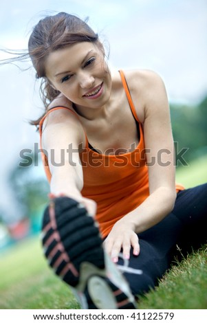 Beautiful girl doing stretching in the park - stock photo