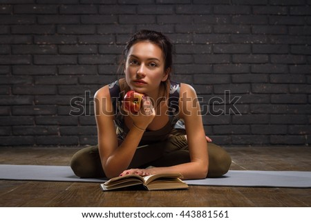 Beautiful Girl Doing Yoga Exercises And Read Book On Brick Wall Background - stock photo
