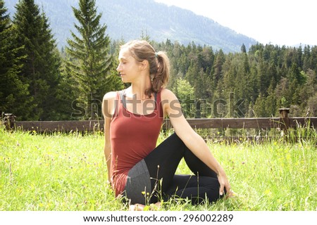 Beautiful girl doing yoga in the long grass - stock photo
