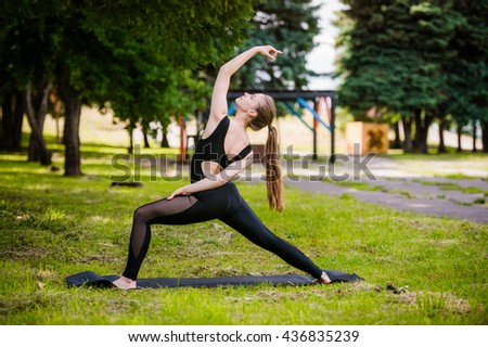 beautiful girl doing yoga on green grass in park at summer morning - stock photo