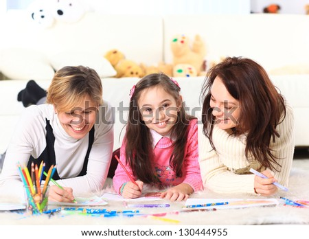 Beautiful girl draws with his mother and aunt.