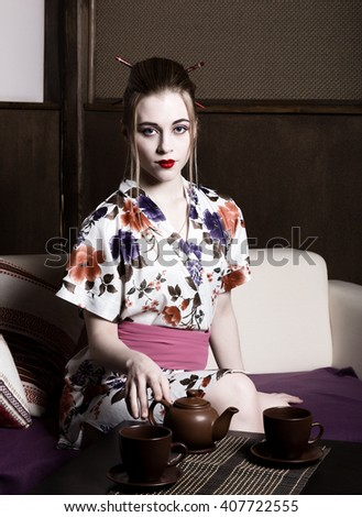 beautiful girl dressed as a geisha and preparing tea ceremony. Geisha makeup and hair dressed in a kimono. The concept of traditional Japanese values - stock photo