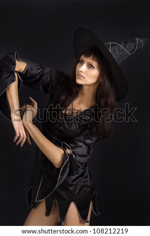 Beautiful girl dressed as a witch on a white background