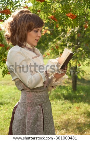 Beautiful girl dressed in old style points to the book that she reads in summer park                                - stock photo