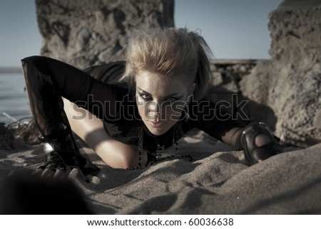 beautiful girl dressed like a rock star as a predator lurking in the sand - stock photo