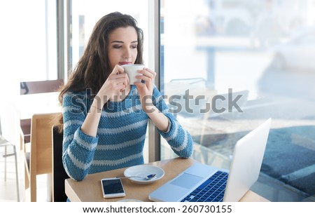 Beautiful girl drinking a coffee at the bar and connecting with a computer - stock photo