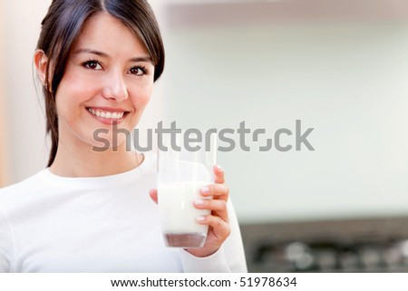 Beautiful girl drinking a glass of milk - stock photo