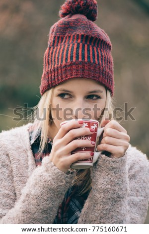 Beautiful girl drinking coffee or tee outdoors. Christmas style mug. Hot beverages.