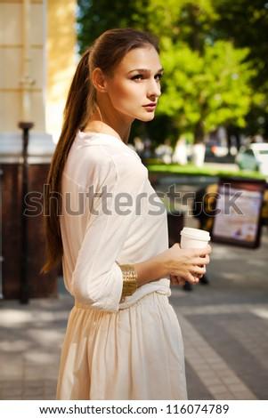beautiful girl drinking coffee, walking around the city - stock photo