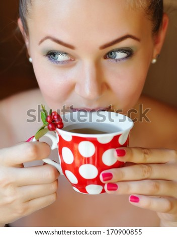 Beautiful girl drinking healthy cowberry tea - stock photo