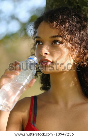 Beautiful girl drinking water after a run