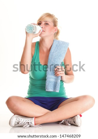 Beautiful girl drinking water from blue bottle isolated on white background