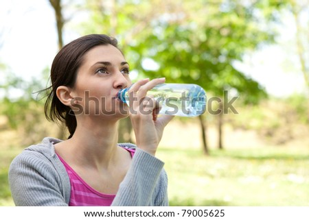 beautiful girl drinking water in the park, close up - stock photo