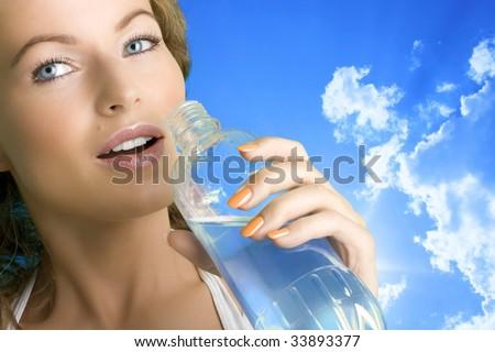 Beautiful girl drinking water outdoors - stock photo