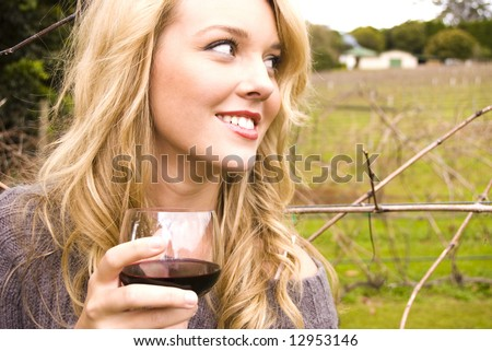 beautiful girl drinking wine at a vineyard - stock photo