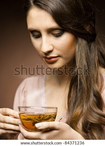 beautiful girl drinks tea  in the kitchen - stock photo