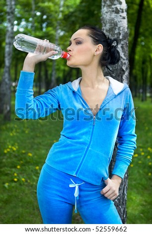 beautiful girl drinks water in park after sport