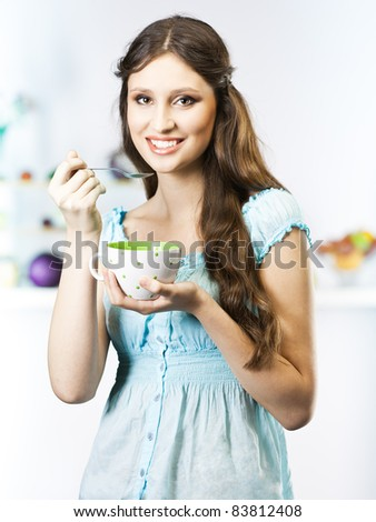 Beautiful girl eat in the kitchen - stock photo