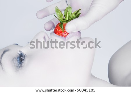 Beautiful girl eating a fresh red strawberry