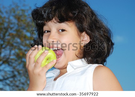 Beautiful girl eating an apple outdoor