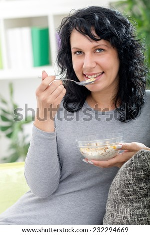 beautiful girl eating cereal and smiling in front of camera