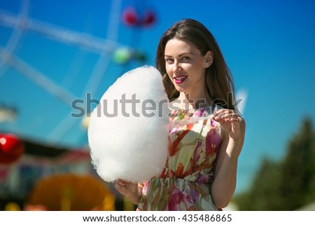 Beautiful girl eating cotton candy at an amusement park - stock photo