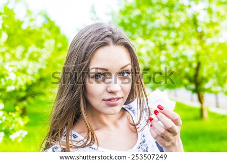 Beautiful girl eating cupcake outdoor on green spring park background Young adult woman enjoying and eat unhealthy food snack in lunch break smiling happy.White cakes - zephyr - stock photo